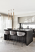 Upholstered bar stools at island counter in modern kitchen decorated in grey