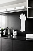 Clothes rail in modern utility room decorated in black and grey