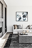 Square ottoman in elegant living room decorated in white and grey