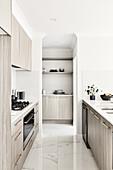 Moderne helle Küche mit grauen Fronten und Marmorfliesenboden