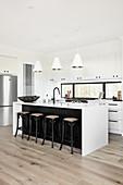Moderne Küche in Schwarz-Weiß mit Barhockern an der Kücheninsel