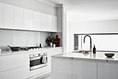 Moderne minimalistische Küche in Weiß mit Hochglanzfronten