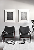 Two grey armchairs below monochrome artworks on wall in living room