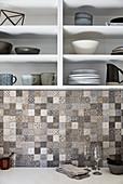 Stoneware crockery on kitchen shelves above mosaic-tiled splashback