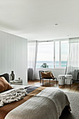 Bohemian-style bedroom in natural shades with panoramic windows