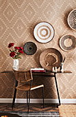 Desk on the wall with ethnic wallpaper and bast bowls