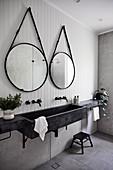 Zwei runde Spiegel überm modernen Waschbecken im grauen Bad