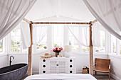 Schlafzimmer mit Fensterfront, Himmelbett und freistehender Wanne