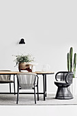 Simple dining room in Boho style with raffia chair and cactus