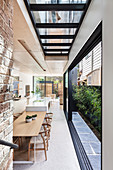 Dining table and kitchen in open-plan interior of architect-designed house