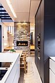 Moderne Wohnküche mit Kücheninsel, Esstisch und Kamin