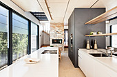 Modern kitchen in narrow architect-designed house with glass wall