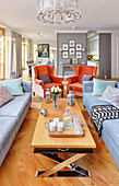 Orange armchairs in elegant, open-plan, classic interior