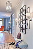 Gallery of pictures above upholstered bench in hallway of elegant apartment