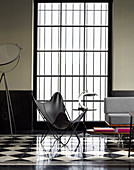 Butterfly chair in front of lattice window in designer living room