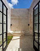 Double doors leading into Mediterranean courtyard with fountain and hammock