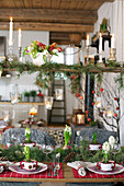 Christmas table and shelf decorated with fir branches and flowers