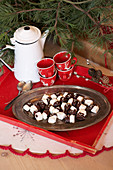 Marshmallows with chocolate icing, cups and jug on red tray