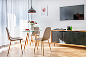 Upholstered chairs around small glass table in interior with wall-mounted TV