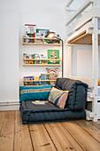 Floor cushions next to bookshelves and bunk beds in children's bedroom