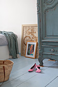 Pink court shoes on pale blue wooden floor in bedroom