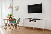 Round table and wall-mounted TV above sideboard in living room