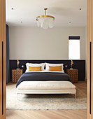 View into symmetrical bedroom with half-height, dark blue panel behind bed