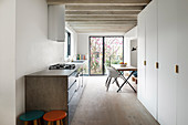 Dining table and fitted cupboards in modern, open-plan kitchen