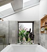 Plants on windowsill in grey, modern bathroom with skylight