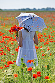 Girl holding bunch of flowers in field of barley and poppies