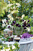 Arrangement of vase of black tulips, lilac flowers, glass cup of espresso and jars of biscuits and rock sugar
