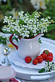 Bouquet of lilies of the valley in creamer pitcher on a plate with strawberries
