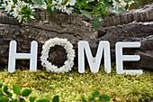 Botschaft HOME mit Kranz aus Fliederblüten und Holzbuchstaben