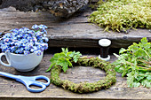 Ingredients for forget-me-not wreath: forget-me-not flowers, cranesbill leaves, moss wreath, scissors and winding wire