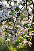 Swallow and wooden heart in a blossoming apple tree