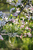 Bouquet of lilies of the valley in a hanging vase hung on a blossoming apple tree