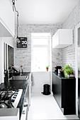Schmale Küche mit schwarz-weißen Möbeln, weißem Boden und weiß gestrichener Backsteinwand