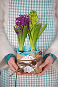 Hands hold hyacinths wrapped in baking paper