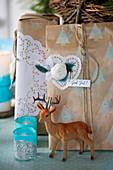 DIY-Weihnachtverpackung mit Tortenspitze, Rehfigur und Windlichter im Vordergrund