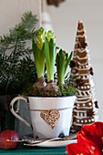 Hyacinths in a jug, behind decorated gingerbread trees