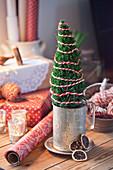 Mini-Weihanchtsbaum mit rot-weißem Garn umwickelt im Zinkgefäß