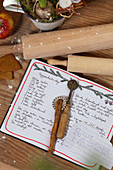 Handwritten baking recipe, pastry wheel and rolling pin
