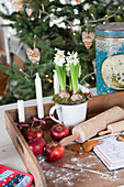 Wooden tray with apples, candles, hyacinths, rolling pin and baking recipe