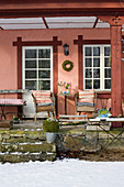 A cosy seating area with wicker chairs on a wintery veranda