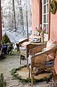 Korbstühle auf Veranda mit Blick in verschneiten Garten