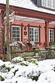 Blick vom verschneiten Garten auf Veranda mit Sitzplatz