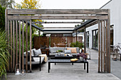 Black tables and outdoor sofas below wooden pergola