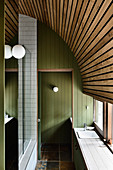 Narrow bathroom with green wood panelling and curved wooden ceiling