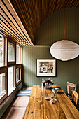 Dining table and bench by window in kitchen with green wood panelling
