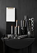 Brennende Kerzen und Papierrollen in Gefäßen auf schwarzem Konsolentisch